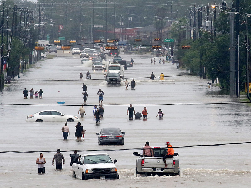 People walk through floodwaters on Telephone Road in Houston on Sunday after 2 feet of rain from Hurricane Harvey pummeled the Gulf Coast. Thomas B. Shea/AFP/Getty Images