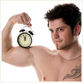 Man Holding an Alarm Clock on His Bicep